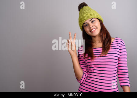 Young beautiful Indian woman wearing knitted hat against gray ba - Stock Photo