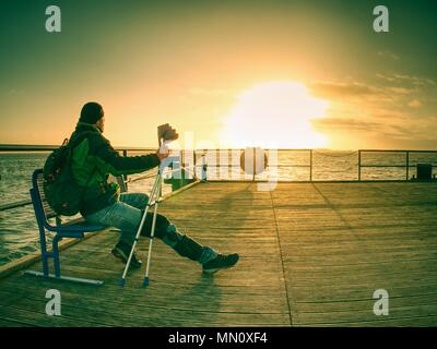 Gloomy nostalgic silhouette of sad lonely melancholic adult man with hooded jacket standing on lake bridge within  early morning and thinking - Stock Photo