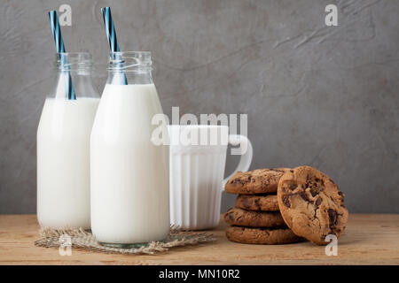 Two bottles of milk and chocolate chip cookies on dark background with copy space - Stock Photo
