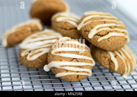 Freshly baked, homemade pumpkin spice cookies, with maple icing. These gluten and dairy free biscuits are displayed on a wire cooling. - Stock Photo