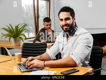 Attractive bearded man in pristine white shirt working on silver laptop, wearing nice big headphones around the neck, two other empoyees doing the task behind the man - Stock Photo