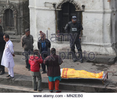 Nepali police stand guard over the body of a high-caste man of importance along the bank of the Bagmati River as preparations are made for his cremati - Stock Photo