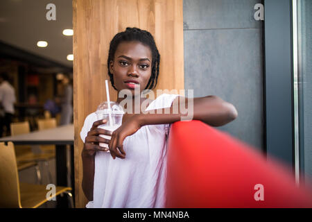 Photo of positive dark skinned afro american female ejoys good rest at coffee shop, drinks beverage. People, leisure and eating concept - Stock Photo