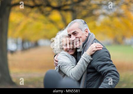 Happy senior couple hugging in autumn park - Stock Photo