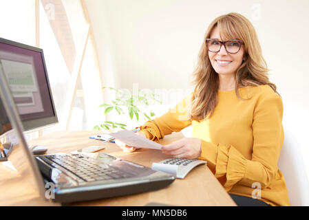 Middle aged executive businesswoman sitting at computer and laptop and doing some paperwork. Home office. - Stock Photo