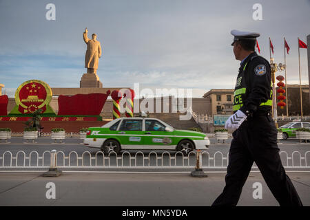 A Chinese policeman walks down the street past a huge monument to Mao Zedong in Kashgar city, Xinjiang Uygur Autonomous Region of China - Stock Photo