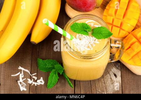 Mango, banana, coconut smoothie in a mason jar glass, overhead view on a rustic wood background - Stock Photo