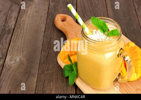 Mango coconut smoothie in a mason jar glass on paddle board against a rustic wood background - Stock Photo
