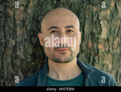 face of a bearded serious bald man in the park. Portrait of a middle-aged man. - Stock Photo