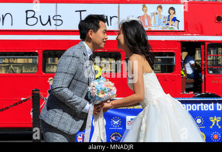Westminster, London, 15th May 2018. An Asian couple have chosen the area opposite the iconic Palace of Westminster as their location for wedding photos, on a beautifully sunny day with blue skies in London. Credit: Imageplotter News and Sports/Alamy Live News - Stock Photo