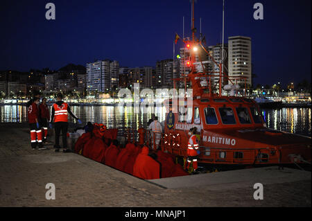 Malaga, Spain. 15th May, 2018. Sub saharan migrants rest on the ground after being rescued in the Mediterranean sea. Members of the Spanish Maritime Safety rescued 54 migrants near the Malaga coast and brought to Malaga Port. In this day, a total of 104 migrants were rescued in the Mediterranean sea. Credit: Jesus Merida/SOPA Images/ZUMA Wire/Alamy Live News - Stock Photo