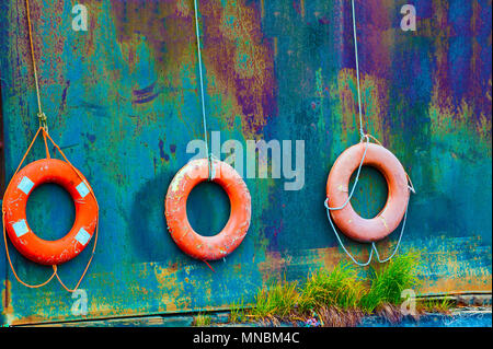Close up image of three life buoys hanging off the side of a rusting vessel left beached on shore where grass is growing in it's seems.  A rustic naut - Stock Photo