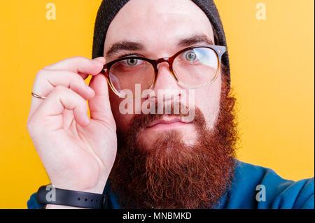Serious bearded man touching eyeglasses - Stock Photo