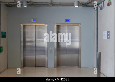 Closed elevators with buttons in corridor with concrete walls. Concept of office center interior - Stock Photo