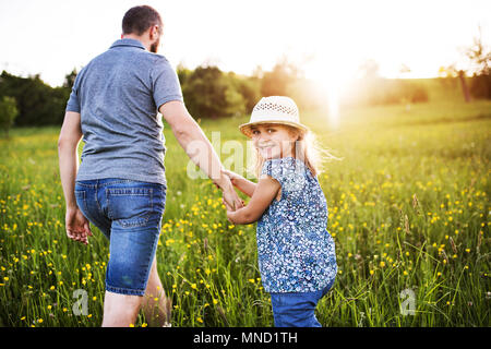 Father with a small daughter on a walk in spring nature. - Stock Photo