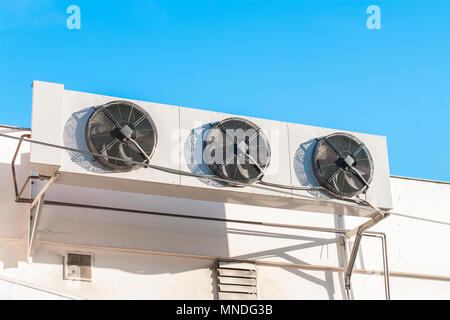 Air compressors installed on the wall of building with sunlight sky. - Stock Photo