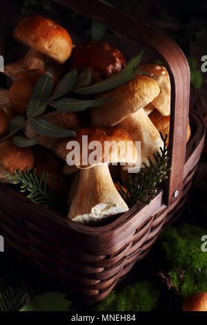 mushrooms porcini in the basket on a wooden background decorated with leaves and moss - Stock Photo