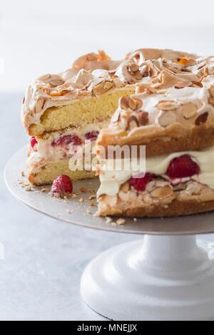Quick cake made from sponge cake, cream and raspberries with a meringue topping on a cake stand - Stock Photo