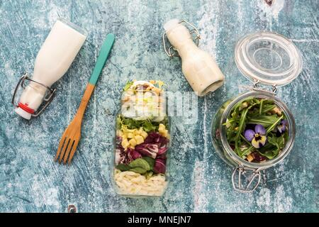 Quinoa and orzo pasta salads in glass jars, with dressing and a wooden fork - Stock Photo