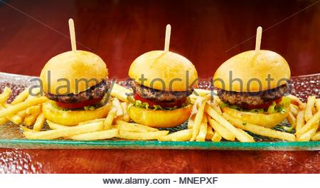 Three mini burgers with chips on a long serving platter - Stock Photo