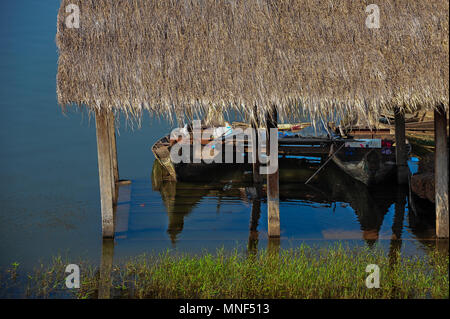 Thatched boat house on a lake in Cambodia - Stock Photo