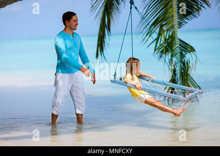Happy father and his adorable little daughter at tropical beach having fun on a swing - Stock Photo