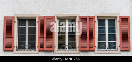 close up view of three windows with wooden window shutters in red - Stock Photo