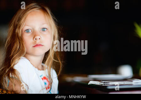 Portrait of adorable little girl with blonde curly hair and green eyes - Stock Photo
