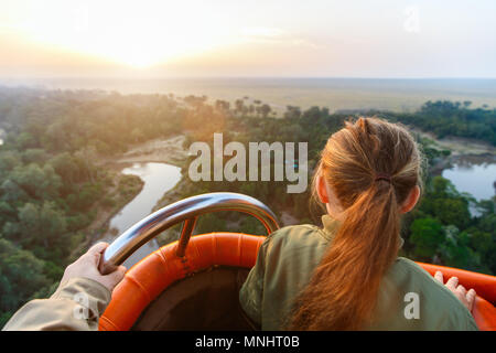 Little girl enjoying early morning flight on hot balloon in Masai Mara national park,  Kenya - Stock Photo