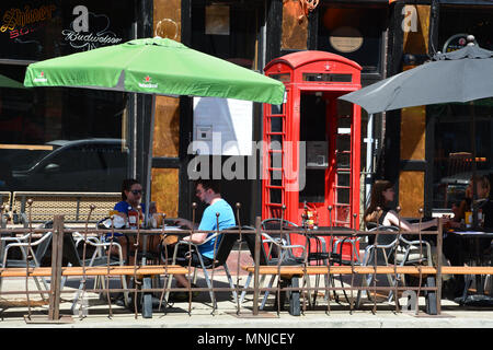 Patrons drink at a sidewalk cafe in the trendy Wicker Park neighborhood of Chicago. - Stock Photo