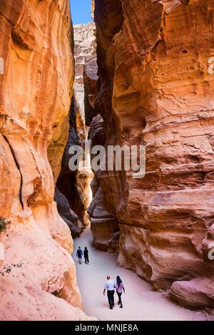 Tourists walking through Al Siq canyon in Petra, Wadi Musa, Maan Governorate, Jordan - Stock Photo