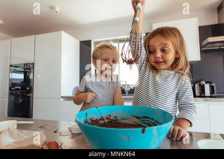 Little girl preparing dough with her brother looking on in kitchen. Girl child whipping chocolate cream with whisk in bowl with brother supervising in - Stock Photo