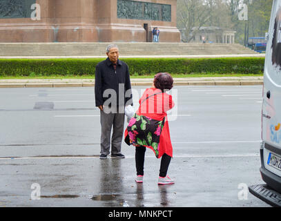 Berlin, Germany - April 14, 2018: Asian tourists take photos against the base of Victory Column in Berlin - Stock Photo