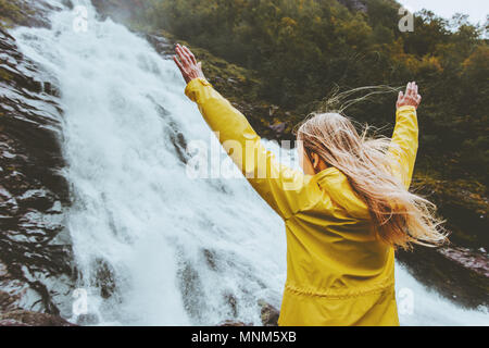 Traveler woman raised hands enjoying waterfall landscape Traveling alone into the wild adventure lifestyle harmony with nature concept emotional expre - Stock Photo