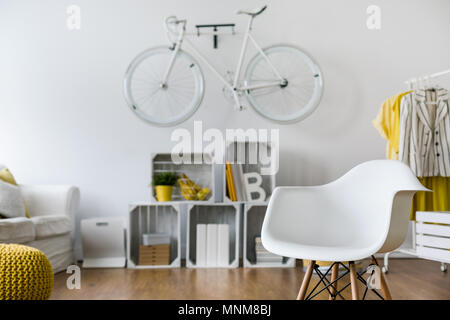 Close-up of white armchair in spacious living room. In the background wooden shelf and bicycle hang on wall - Stock Photo