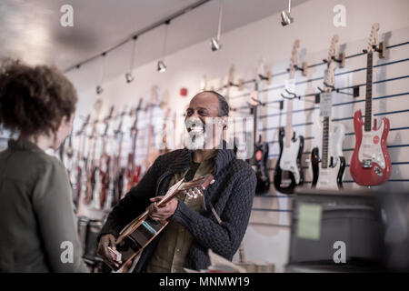 Senior male playing guitar in store - Stock Photo
