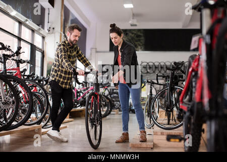 Small business owner serving customer in a bike store - Stock Photo
