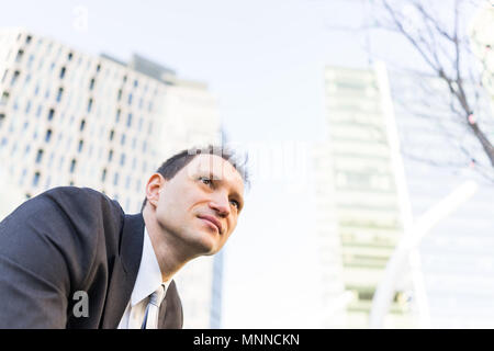 Handsome, attractive young businessman sitting smiling looking up in suit and tie, cheerful on interview break in urban park, skyscrapers - Stock Photo