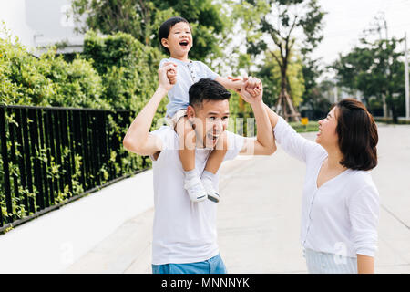 Cute Asian father piggybacking his son along with his wife in the park. Excited family raising hands together with happiness - Stock Photo