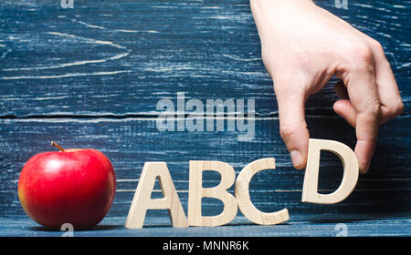 Red apple and letters ABCD. The hand puts the letter D in the alphabet order. Apple for the teacher. The concept of teaching and education. School, co - Stock Photo