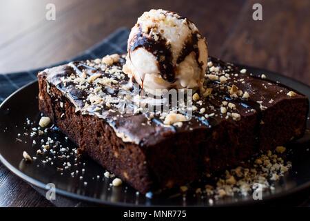 Chocolate Brownie with Ice Cream and Hazelnut Powder. Dessert Concept. - Stock Photo
