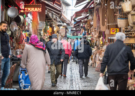 Shoppers walk along busy narrow street of outdoor marketplace selling various goods, Istanbul, Turkey - Stock Photo
