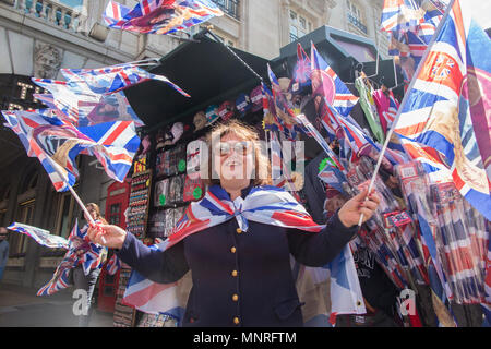 A woman waves a flag at a souvenir stall on Piccadilly in London to celebrate the marriage of Harry and Meghan Markle - Stock Photo