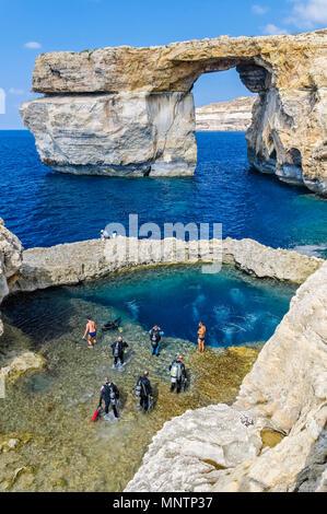 scuba divers and swimmers at Blue Hole, Azure Window, or Dwejra Window in background, Gozo, Malta, Mediterranean Sea, Atlantic Ocean - Stock Photo