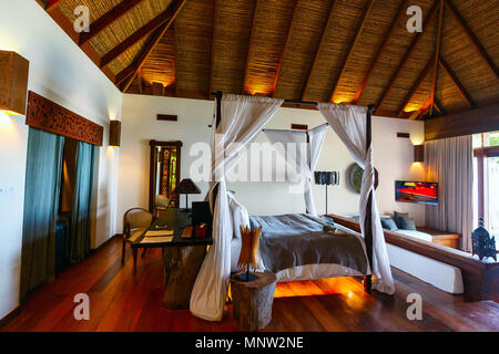 Tropical bedroom interior with double bed in a luxury resort - Stock Photo