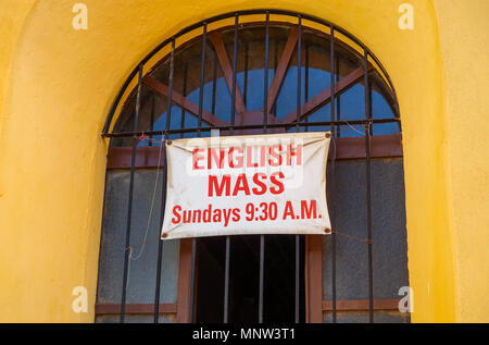 A sign in the window of a Catholic Church in San Miguel de Allende, Mexico announcing a mass in English - Stock Photo