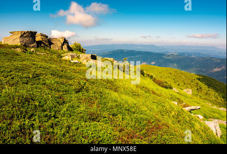 mountainous landscape in summer. lovely scenery with rocky formation on the grassy hill under the blue sky with some clouds. - Stock Photo