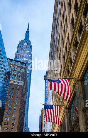 United States flags fly with the Empire State building in the background in New York City, USA. - Stock Photo