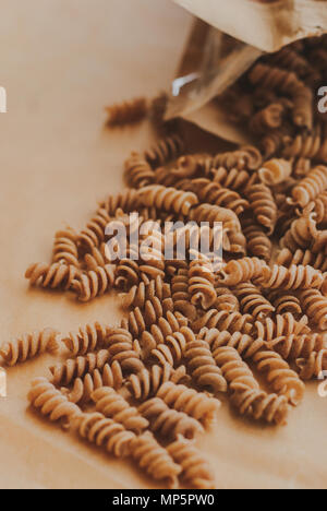 wholemeal pasta fusilli from organic whole grain spelt falling from a paper bag - Stock Photo