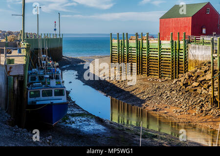 Fishing boats resting on the ocean floor at low tide in Hall's Harbour, Nova Scotia, Canada. - Stock Photo